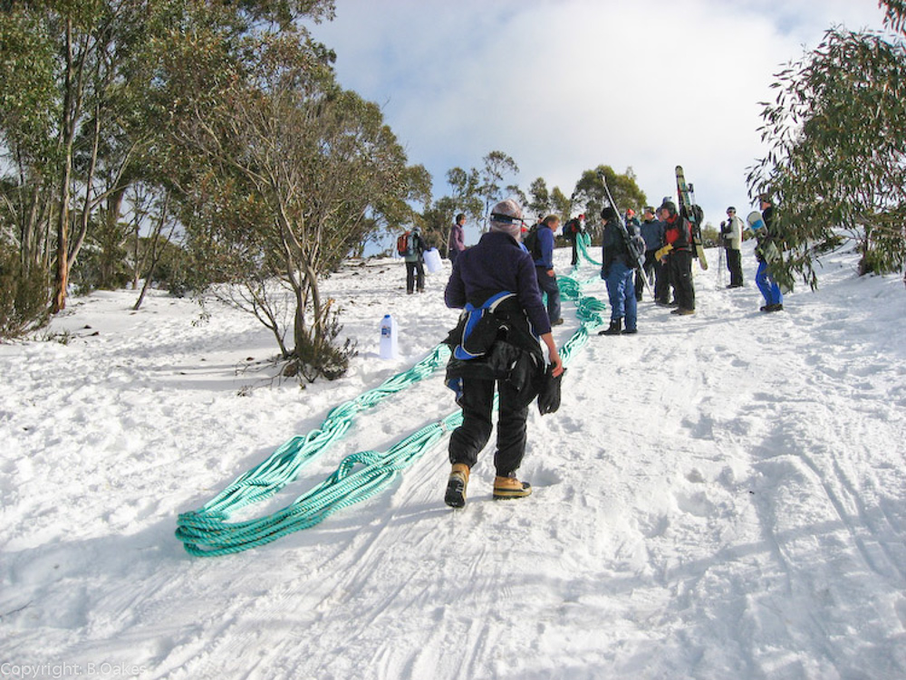 image of STSA volunteers bringing a new tow rope up the mountain during winter for an emergency repair