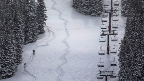 skiers on Alpine Touring gear are walking up a closed ski resort slope